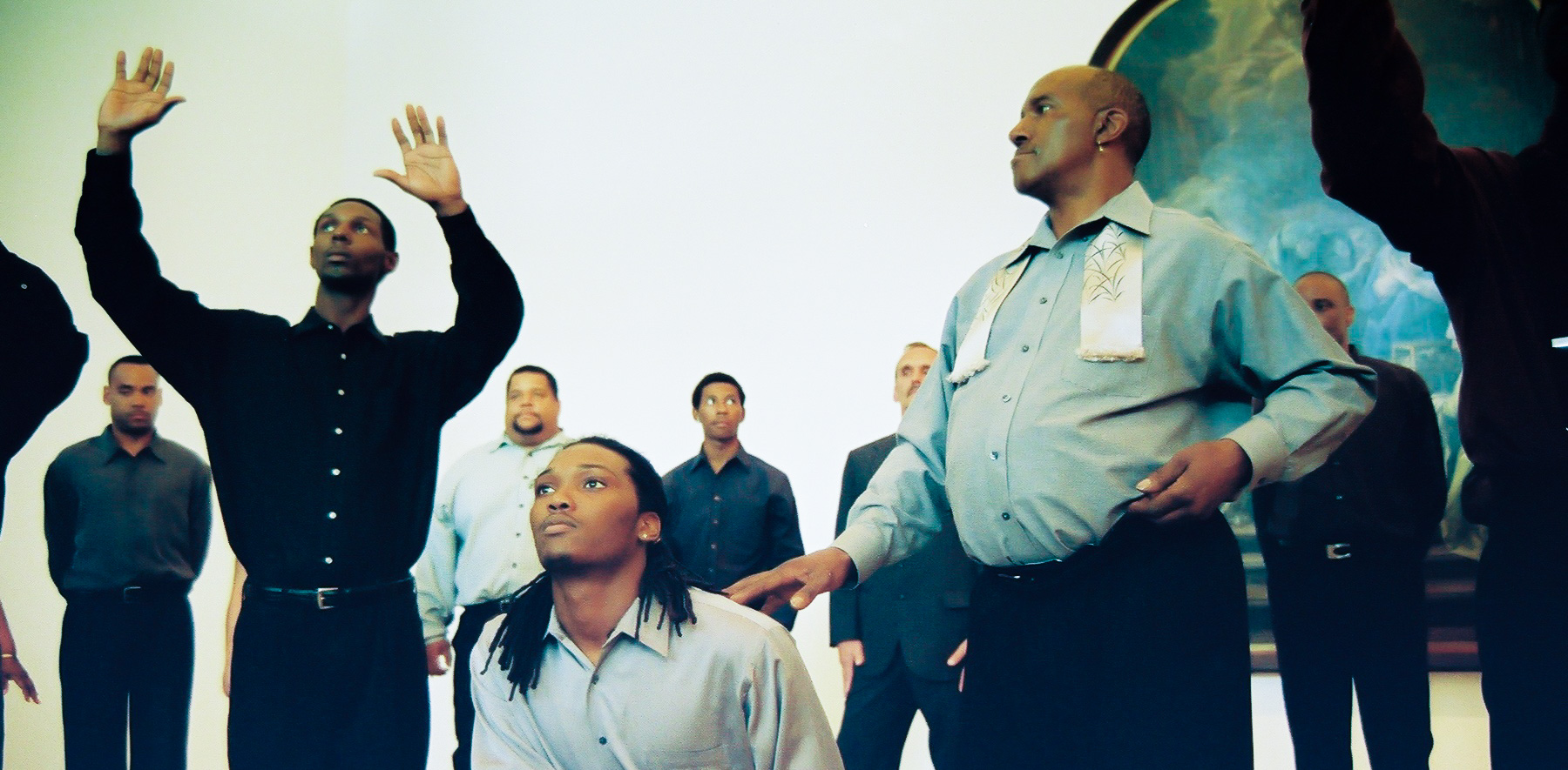 Participants pose and perform for an audience. One kneels, another rests their fingers on the kneeler's shoulder, and others raise their hands with their palms foreword.