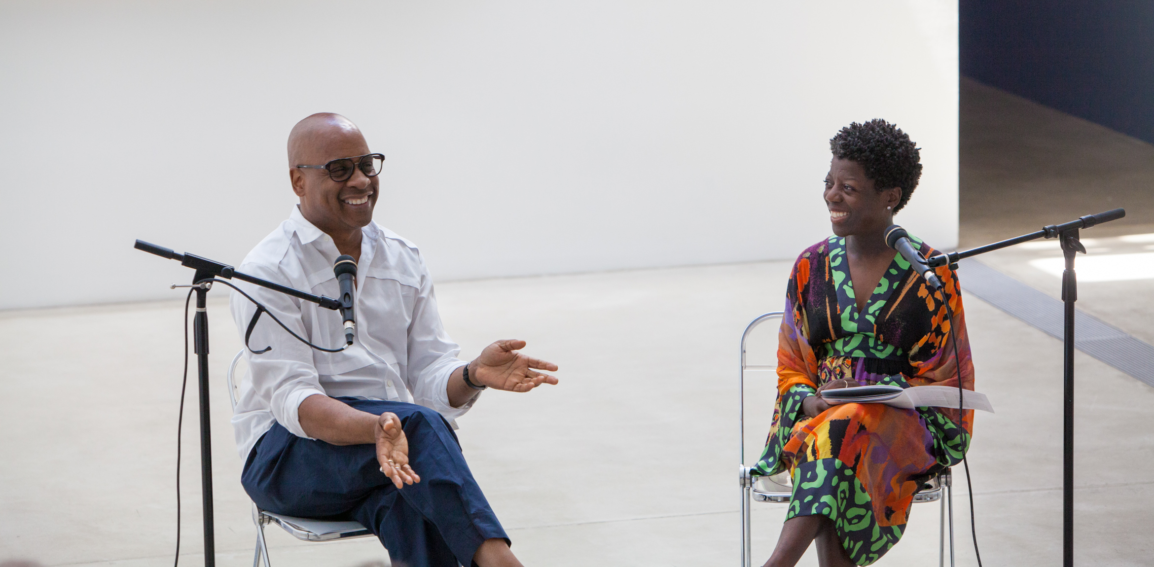 Glenn Ligon and Thelma Golden converse in front of microphones in the Lower Main Gallery.