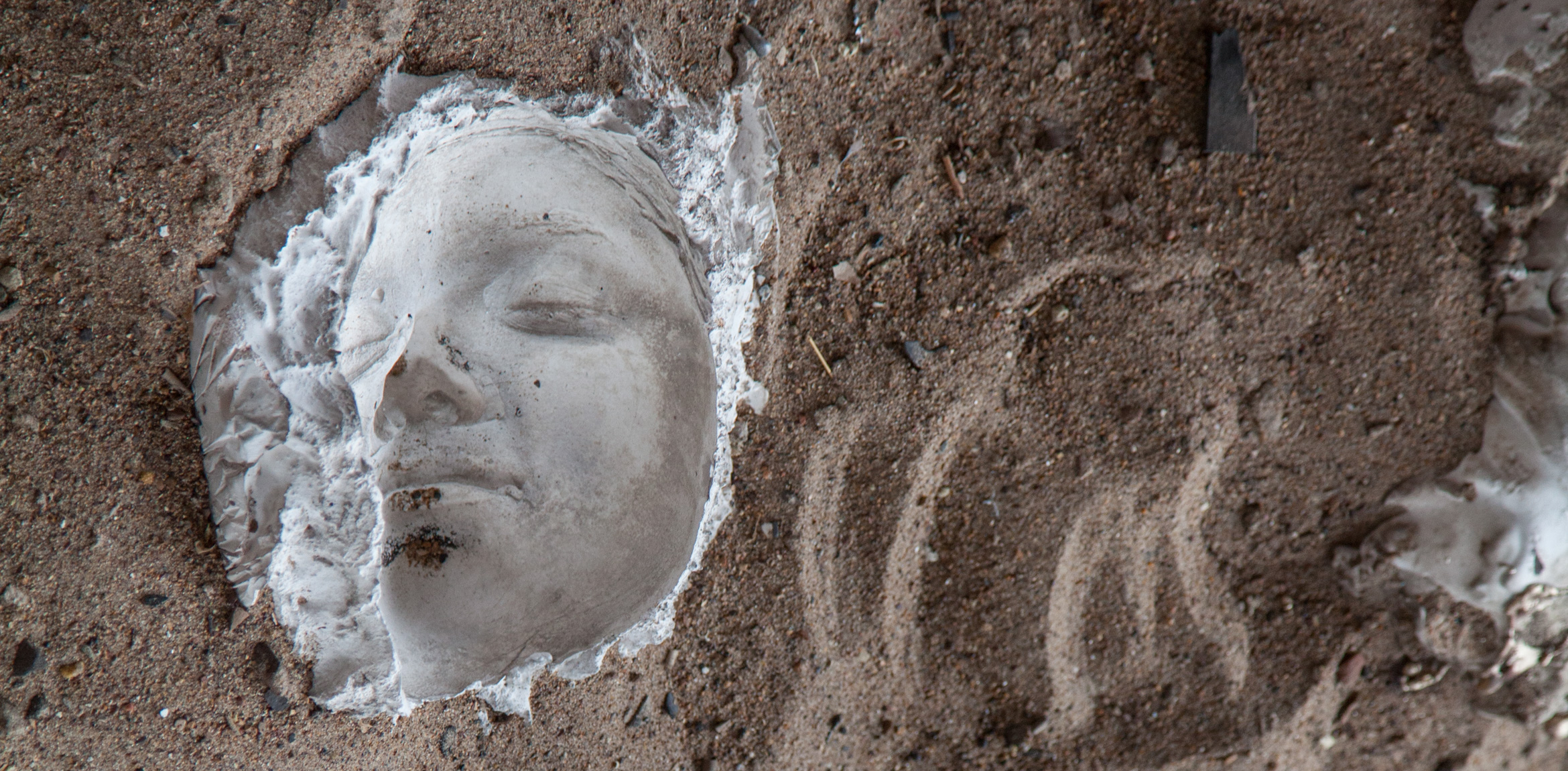 A closeup of a plaster sculpture of a face surrounded by dirt and sand.