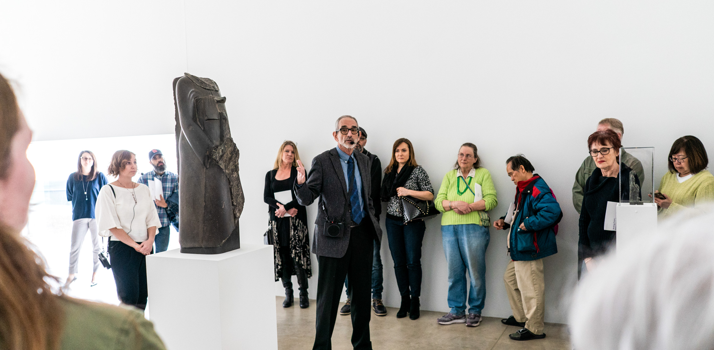 Ed Bleiberg speaks in the Main Gallery to a large circle of attendees, gesturing at a beheaded Egyptian sculpture.