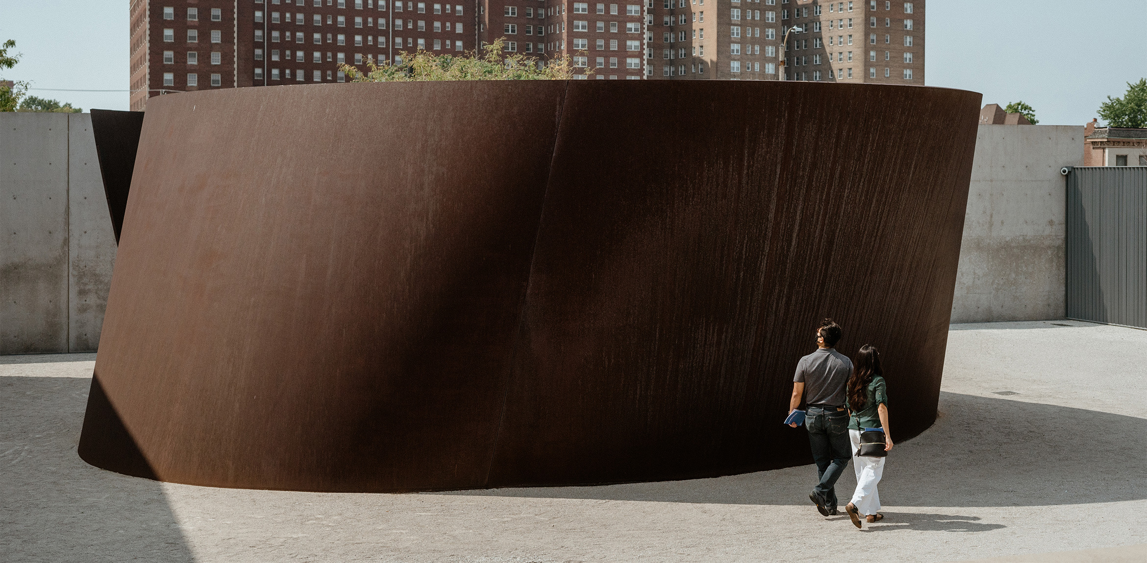 Two visitors walking around the base of Richard Serra's Joe in the museum courtyard